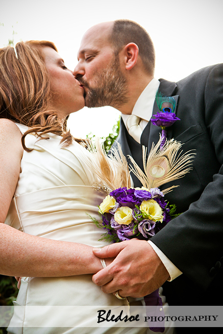 """Bride kissing her groom holding a peacock feather bouquet"""