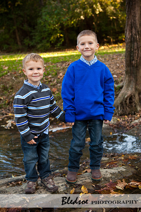 """Brothers standing in a creek."""