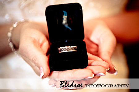 Bride holding groom's wedding ring.