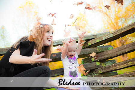 """Allie and mommy tossing fall leaves"""