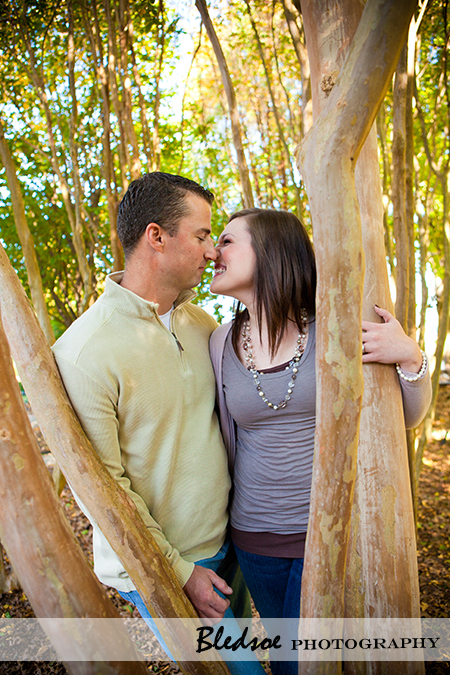 """Amy and Scott laugh under the trees at UT Gardens"""