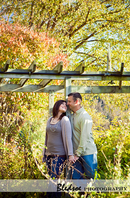 """Amy and Scott snuggle under the arbor at UT Gardens"""