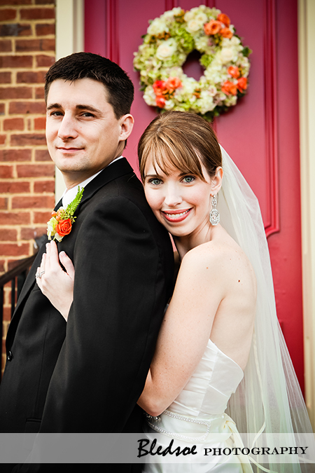 """Bride and groom pose in front of red door"""