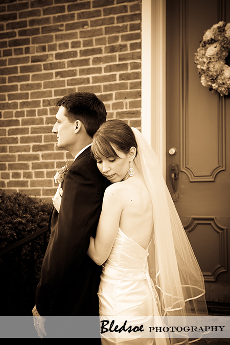 """Bride hugging groom in sepia"""