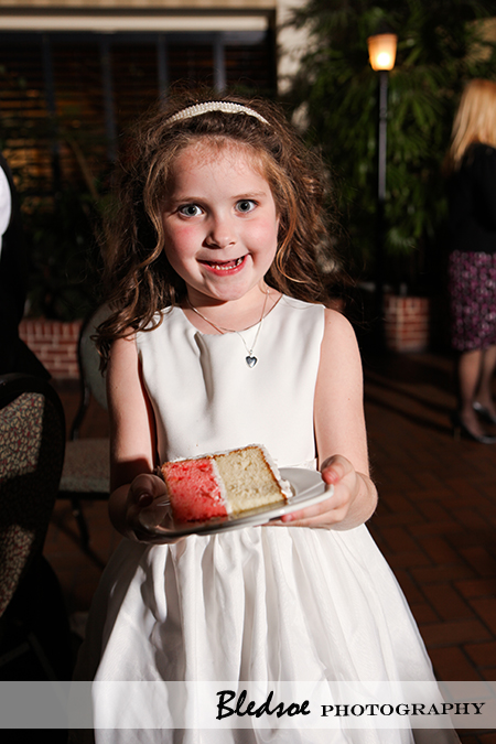 """Flower girl holding a piece of wedding cake"""