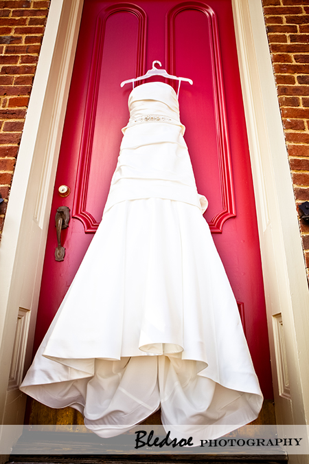 """Wedding dress hanging on red church door"""